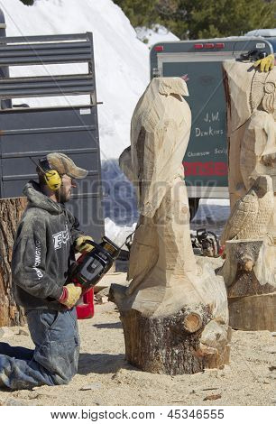 Man Using Chainsaw To Carve An Eagle Wood Carving