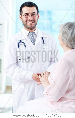 Confident doctor with senior patient looking at camera with smile