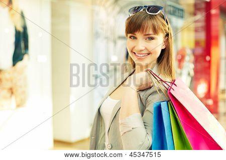 Retrato de uma menina de compra com paperbags
