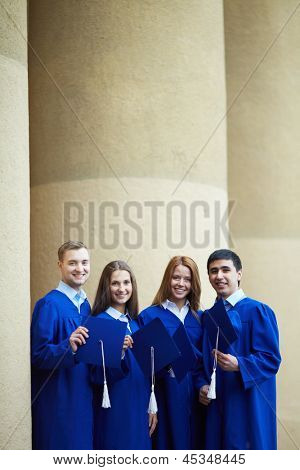Group of smart students in graduation gowns and hats in hands looking at camera