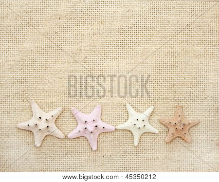Background with starfishes on canvas texture