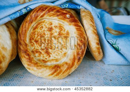 Traditional eastern lepeshka nan - white flat bread baked in old stove