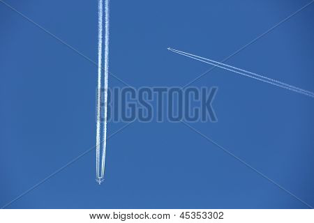 Two jets about to cross leaving smoke trails