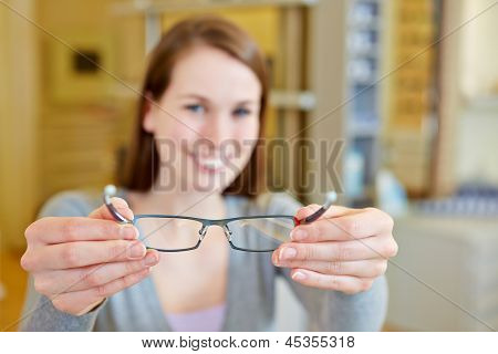 Young woman holding new glasses in optician store