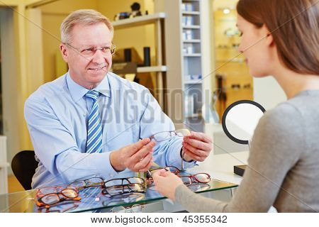 Young woman getting a consultation from an optician for new glasses