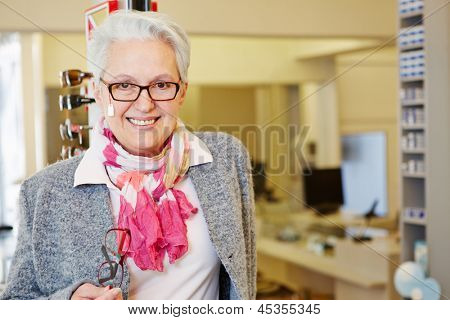 Happy senior woman with new glasses at the optician