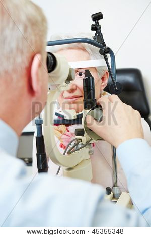 Ophthalmologist using slit lamp to check eye of senior woman