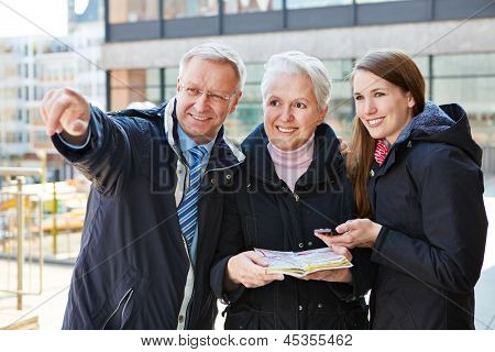 Family with map on sightseeing tour on a city trip