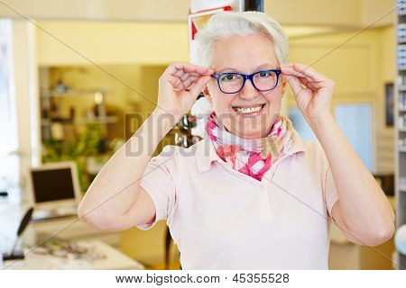 Happy senior woman with her new glasses at the optician