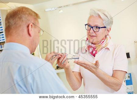 Elderly customer buying new glasses at the optician