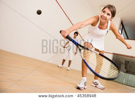 Beautiful woman playing a match of squash