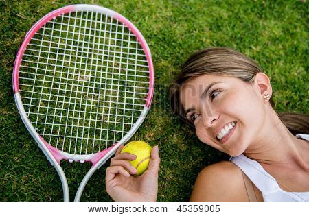 Tennis player lying on the floor with racket and ball - portrait