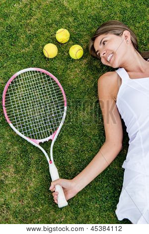 Female tennis player lying on the floor with racket and balls