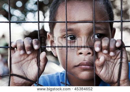 Asian boy from impoverished area, behind and clinging to fence in the Philippines.