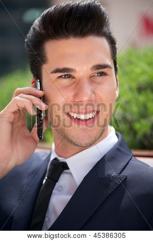 Handsome Young Businessman Talking On Phone Outdoors