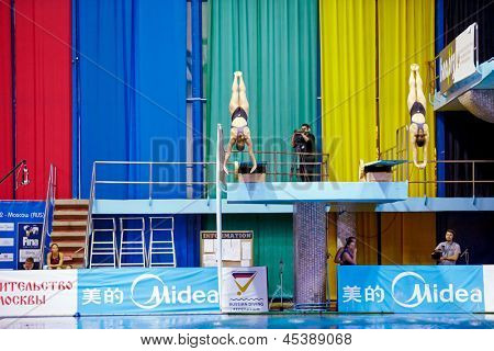 MOSCOW - APR 13:  Female athletes perform syncronized jump from springboard at Pool of SC Olympic on day of third phase of the World Series of FINA Diving, April 13, 2012, Moscow, Russia.