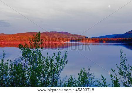 Noite do brilho do sol na calma Twin Lakes Yukon Canadá
