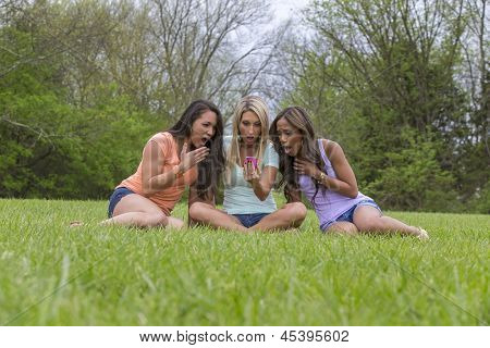 Three young women enjoying a day at the park on their cell phones.