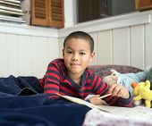 Elementary School Age Boy Reading In Bed With Workbook