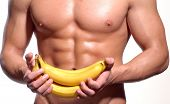 stock photo of light weight  - Shaped and healthy body man holding a fresh bananas - JPG