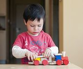 foto of playgroup  - Portrait of a small child playing with colorful wooden toy train - JPG