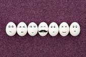 stock photo of collate  - Seven eggs with different facial expressions are lying on the decorative purple sand - JPG