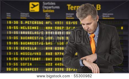 Flight delay. Businessman looking at his watch