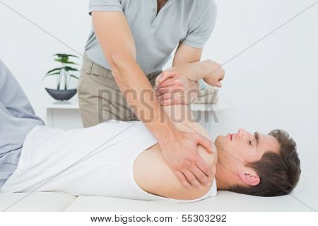 Male physiotherapist examining a young mans hand in the medical office