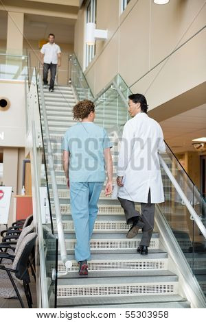Rear view of doctor and nurse climbing up stairs in hospital