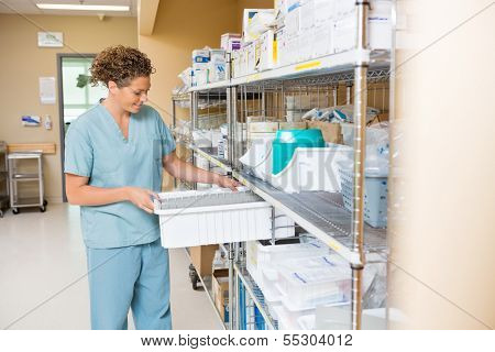 Mid adult female nurse arranging container on shelf in hospital storage room