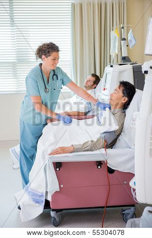 Female nurse covering patient undergoing renal dialysis with blanket in hospital room