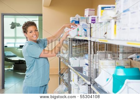 Portrait of female nurse smiling while working in storage room of cancer hospital