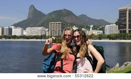 Couple of female backpackers making a self portrait in Rio de Janeiro with Christ the Redeemer in background.