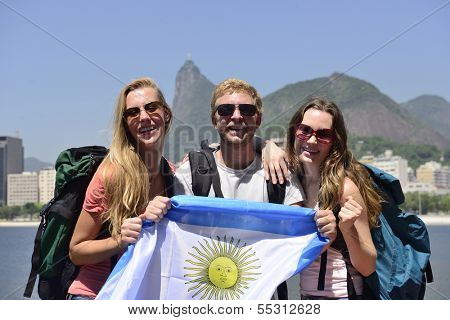 Group of sport fans friends traveling at Rio de Janeiro holding Argentinian flag, with Christ Redeemer in the background.