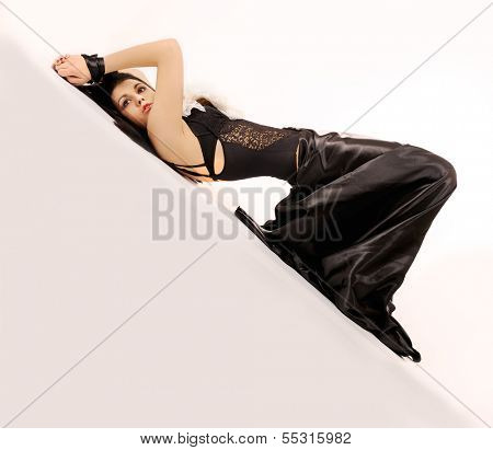 Attractive binding woman dressed in black laying on white background.