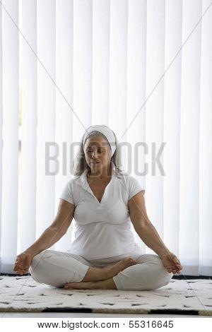 Senior woman doing yoga in white tracksuit