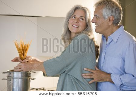 Happy senior couple cooking pasta