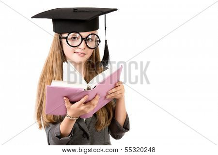 Portrait of a pretty ten years girl in big round spectacles and academic hat reading a book. Isolated over white.