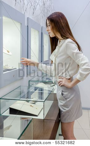 Half-length portrait of girl looking at jewelry in showcase at jeweler's shop. Concept of wealth and luxurious life