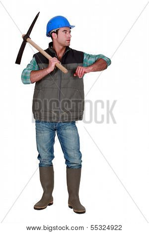 Construction worker with a pickaxe leaning on empty copyspace