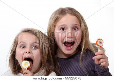 Little girls with lollipops