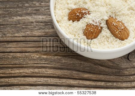 almond flour high in protein, low in carbohydrates, low in sugars and gluten free - a ceramic bowl on grained wood background