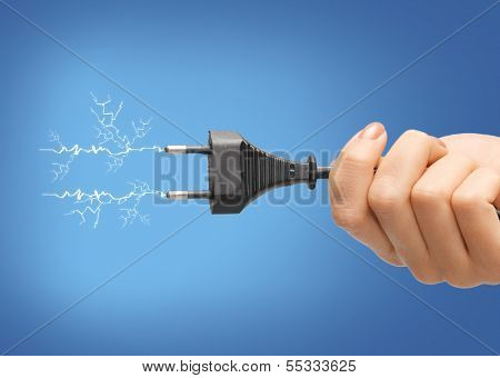 electricity concept - close up of hand holding black electrical plug with wire