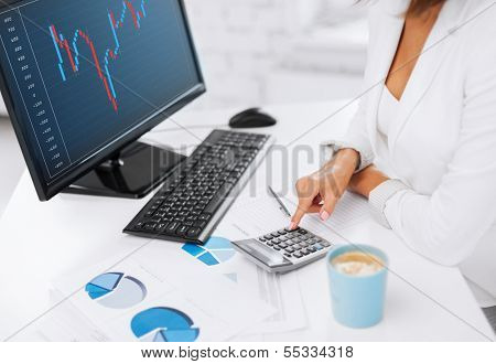 business, office and money concept - woman hand with calculator, papers, monitor and forex chart on screen