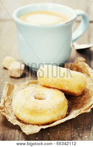 Coffee break with fresh sugary donuts over white background