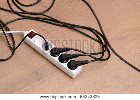 Overloaded power board, on wooden floor background