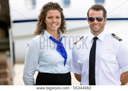 Portrait of confident stewardess and pilot standing against private jet