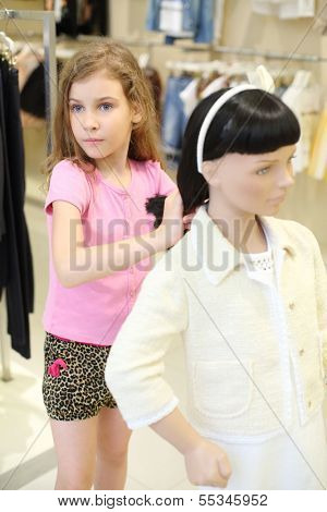 Little pretty girl in shorts touches hair of dummy and looks away in children store.