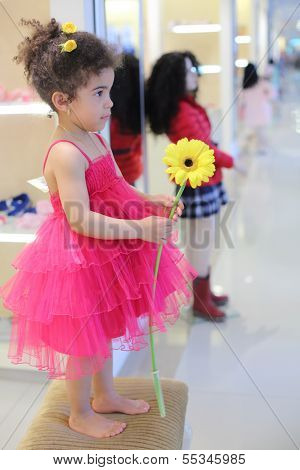 Little barefoot girl with flower stands on pouf in children store.