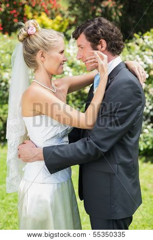 Happy wife touching her new husbands cheek in the countryside